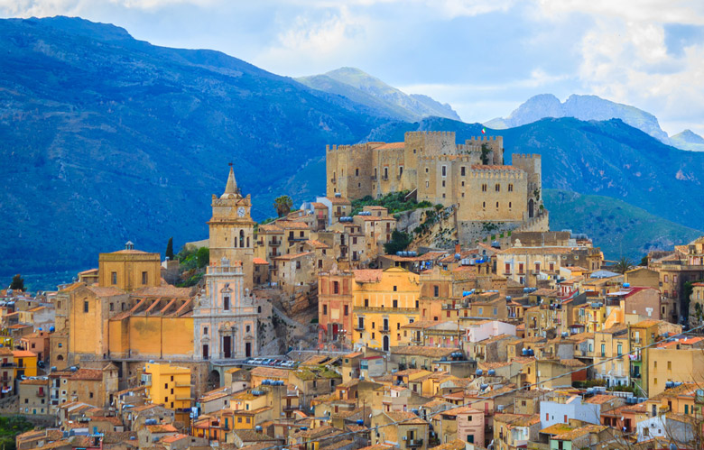 View of Caccamo town on the hill with mountains background on cloudy day in Sicily